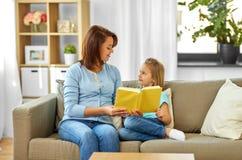 Muchacha feliz con el libro de lectura de la madre en casa foto de archivo libre de regalías