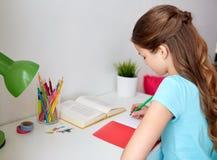 Muchacha feliz con el libro que escribe al cuaderno en casa Fotografía de archivo libre de regalías