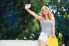 Muchacha feliz con el monopatín que hace la foto del selfie Imagen de archivo libre de regalías