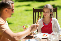 Muchacha feliz con el padre que come en el jardín del verano Fotos de archivo