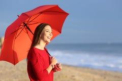 Muchacha feliz con el paraguas rojo en la playa Foto de archivo libre de regalías