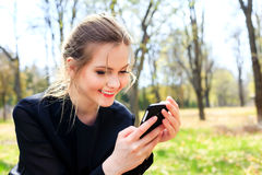 Muchacha feliz con el pelo despeinado que mira en la sonrisa del smartphone Imagen de archivo libre de regalías