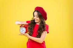 Muchacha feliz con el pelo rizado largo en boina Ni?o con el reloj de alarma Moda intemporal niño parisiense en amarillo belleza imagen de archivo libre de regalías
