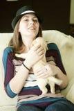 Muchacha feliz con el perrito divertido en el sofá Imagen de archivo
