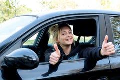 Muchacha feliz con el pulgar para arriba que conduce su nuevo coche Foto de archivo