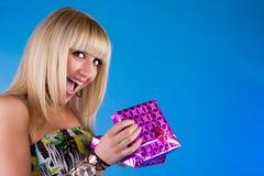 Muchacha feliz con el rectángulo de regalo sobre azul Foto de archivo