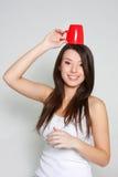 Muchacha feliz con el sombrero de la taza de té roja Foto de archivo