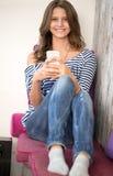 Muchacha feliz con el teléfono elegante Imagen de archivo