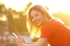 Muchacha feliz con el teléfono elegante en la puesta del sol Foto de archivo