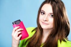 Muchacha feliz con el teléfono móvil en cubierta rosada Foto de archivo