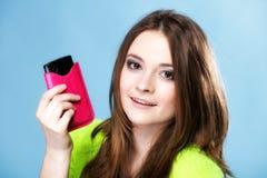 Muchacha feliz con el teléfono móvil en cubierta rosada Fotos de archivo libres de regalías