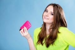 Muchacha feliz con el teléfono móvil en cubierta rosada Fotografía de archivo