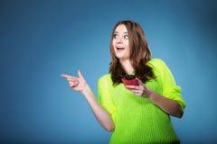 Muchacha feliz con el teléfono móvil que señala el copyspace Imágenes de archivo libres de regalías