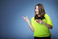 Muchacha feliz con el teléfono móvil que señala el copyspace Imagenes de archivo