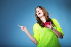 Muchacha feliz con el teléfono móvil que señala el copyspace Fotografía de archivo