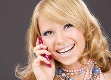 Muchacha feliz con el teléfono rosado Imagenes de archivo