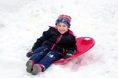 Muchacha feliz con el trineo rojo del platillo Fotos de archivo