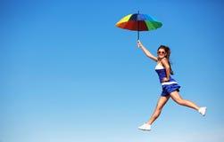 Muchacha feliz con el vuelo colorido del paraguas en el cielo azul Foto de archivo libre de regalías