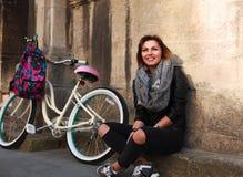 Muchacha feliz con la bicicleta del vintage en ciudad vieja Imagen de archivo libre de regalías