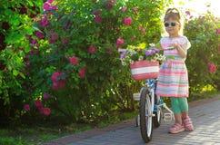 Muchacha feliz con la bicicleta en el jardín Foto de archivo libre de regalías