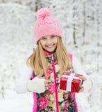 Muchacha feliz con la caja de regalo roja que muestra los pulgares para arriba Imágenes de archivo libres de regalías