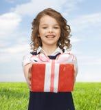 Muchacha feliz con la caja de regalo roja sobre prado del verano Imágenes de archivo libres de regalías