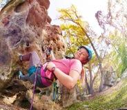 Muchacha feliz con la escalada de la ventaja en área del bosque Imagen de archivo