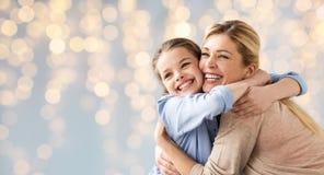Muchacha feliz con la madre que abraza sobre luces Fotografía de archivo