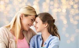 Muchacha feliz con la madre que abraza sobre luces Fotos de archivo libres de regalías