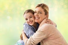 Muchacha feliz con la madre que abraza sobre luces Imágenes de archivo libres de regalías