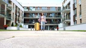 Muchacha feliz con la maleta que sale el hogar por vacaciones almacen de video