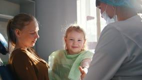 Muchacha feliz con la mamá en una silla dental en la recepción en el dentista almacen de metraje de vídeo