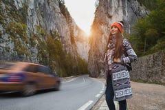 Muchacha feliz con la mochila en montañas cerca del camino Fotografía de archivo