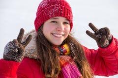 Muchacha feliz con la muestra de la victoria en el paisaje del invierno Foto de archivo libre de regalías