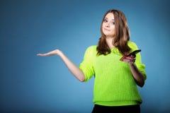 Muchacha feliz con la palma abierta del teléfono móvil para el producto Fotografía de archivo libre de regalías