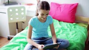 Muchacha feliz con la PC de la tableta que se sienta en cama en casa metrajes