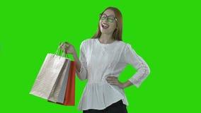 Muchacha feliz con las bolsas de papel después de hacer compras en una venta en una alameda en un fondo verde aislado almacen de video