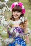 Muchacha feliz con las flores en la cabeza en jardín Foto de archivo libre de regalías