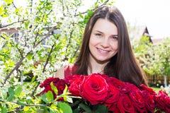 Muchacha feliz con las flores en primavera Imágenes de archivo libres de regalías
