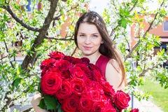 Muchacha feliz con las flores en primavera Foto de archivo