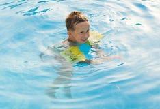 Muchacha feliz con las gafas en piscina Foto de archivo