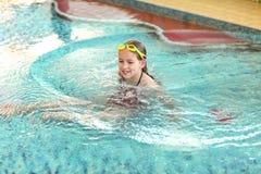 Muchacha feliz con las gafas en piscina Foto de archivo libre de regalías