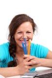Muchacha feliz con las plumas y los lápices en manos Fotos de archivo libres de regalías