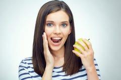 Muchacha feliz con los apoyos dentales que sostienen la manzana verde Foto de archivo libre de regalías