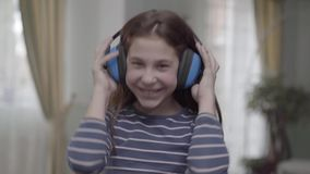 Muchacha feliz con los auriculares que bailan y que escuchan la música almacen de video