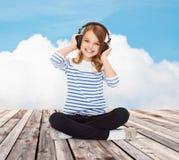 Muchacha feliz con los auriculares que escucha la música Foto de archivo libre de regalías