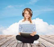 Muchacha feliz con los auriculares y PC de la tableta Fotos de archivo libres de regalías
