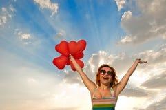 Muchacha feliz con los baloons en forma de corazón Foto de archivo libre de regalías