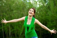 Muchacha feliz con los brazos abiertos al aire libre. Imagen de archivo