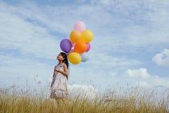 Muchacha feliz con los globos coloridos Imágenes de archivo libres de regalías